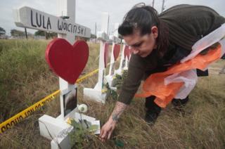 Joyce Mires leaves flowers at a memorial.