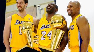 Kobe Bryant and team mates holding their trophies.