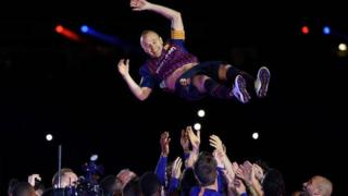 Andres Iniesta is thrown into the air by his Barcelona team-mates