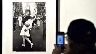 """A visitor takes a snapshot of VJ Day in Times Square, New York, 1945"""" by Alfred Eisenstaedt in Rome on April 30, 2013"""