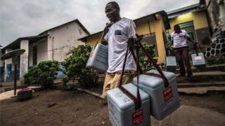 men carry cooler boxes of vaccines down the steps outside a building with a corrugated tin roof