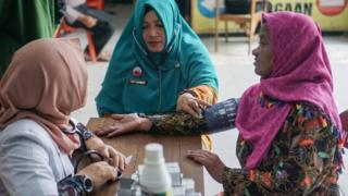 Petugas medis Puskesmas memeriksa tekanan darah petugas Panitia Pemilihan Kecamatan (PPK) yang bertugas melakukan proses rekapitulasi suara Pemilu 2019 di Kecamatan Colomadu, Karanganyar, Jawa Tengah, Selasa (23/04).