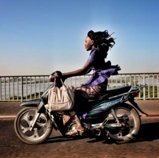 A woman riding a motorbike