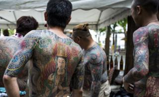 Yakuza members display their tattoos at the Sanja Matsuri Festival in Tokyo's Asakusa district, on May 14, 2016.