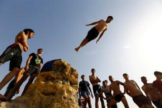 A crowd of people watch a boy diving