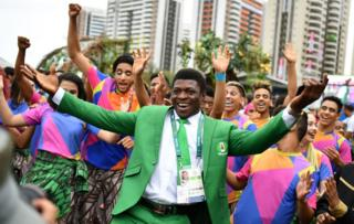 """Nigerian wrestler Soso Tamarau joins dancers performing during a welcoming ceremony for Nigeria""""s Olympic team at the Athletes"""" Village ahead of the Rio 2016 Olympic Games in Rio de Janiero on August 3, 2016"""