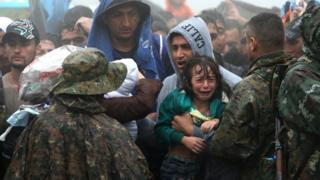 Migrants and refugees wait in the rain to cross the Greek-Macedonian border near the village of Idomeni, in northern Greece on 10 September 2015