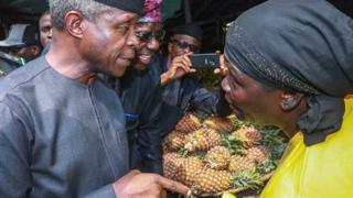 Nigeria Vice President Yemi Osinbajo and one fruit trader