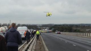 Air ambulance hovering in the sky above a lorry and car crash