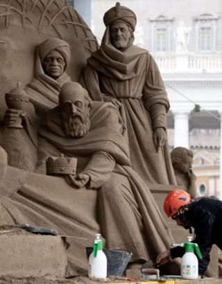 Czech artist Radovan Zivny sculpts a nativity scene from sand at Piazza San Pietro in The Vatican