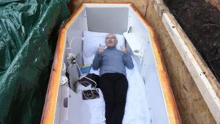 John Edwards dans le confort de son cercueil enterré dans la cour des jardins de l'église Willowfield, à l'est de Belfast