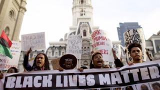 Protesters march past City Hall during a demonstration over the death of Freddy Gray outside City Hall on 30 April in Philadelphia, Pennsylvania.
