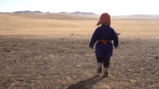 一名蒙古牧民男孩在干枯的草原上奔跑