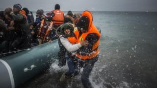 Refugees and migrants disembark on a beach after crossing a part of the Aegean sea from Turkey to the Greek island of Lesbos, on 3 January 2016