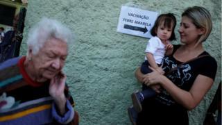 Idosa, mãe e bebê são fotografadas perto de placa indicando local de vacinação
