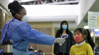 A health worker holds up infrared thermometer to a young girl at Jomo Kenyatta International Airport, Nairobi, Kenya - Wednesday 29 January 2020