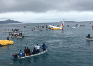 Small boats surround the Air Niugini plane in the water
