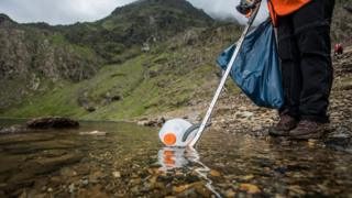 A milk bottle being picked up by a litter picker
