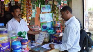 Shopkeeper Anand Talekar and a Mondelez salesman