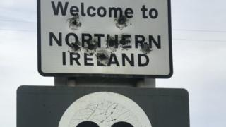 bullet holes riddle the Welcome to NI sign