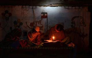 Two Indian girls study by candlelight
