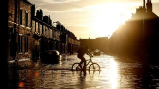 Cyclist passing through flood water
