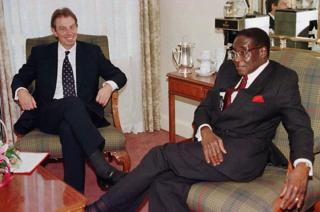 Tony Blair chats with President Robert Mugabe of Zimbabwe 24 October 1997 in Edinburgh, before the start of the Commonwealth Heads of Government meeting.