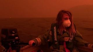 Um menino australiano usa máscara e colete salva-vidas em um barco no lago Mallacoota, após sua família ter fugido para a água para escapar do incêndio florestal que ameaçava a cidade em 31 de dezembro de 2019