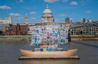 A boat with multi-coloured sails is scene on the Thames river