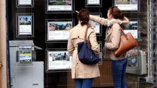 Women look in estate agent window