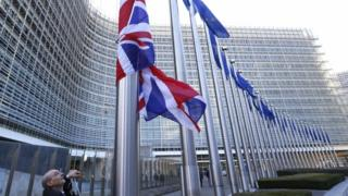 A Union Jack flag next to European Union flags at the EU Commission headquarters in Brussels