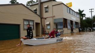 Residents use a boat to travel down a street in Billinudgel, New South Wales.