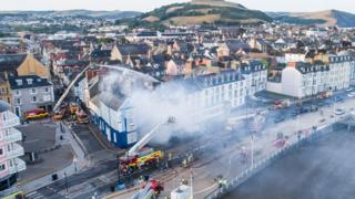Aerial view of Aberystwyth with fire engines damping down the hotel