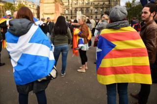 Люди, завернутые во флаги Шотландии и Каталонии