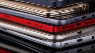 A stack of smartphones in various colours