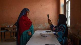 An Independent Election Commission officia scans a voter's face with a biometric device at a polling station in Mazar-i-Sharif on 28 September 2019