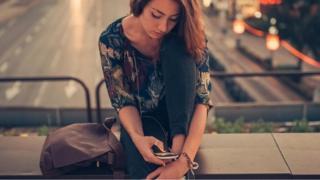 Perempuan menatap ponsel