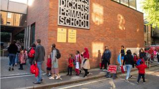 Pupils on their first day back to school at Charles Dickens Primary School, in London, queued outside with their parents at drop off time.