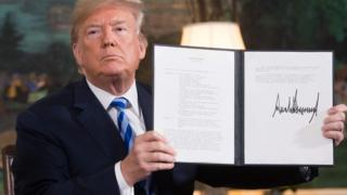In this file photo taken on May 08, 2018 US President Donald Trump signs a document reinstating sanctions against Iran