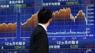 Man in front of board at Tokyo stock exchange
