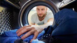 Man looking into washing machine