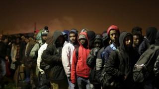 移転手続きのため列を作る移民たち