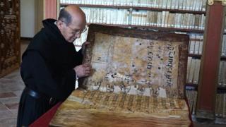 Un monje examina uno de los códices en la biblioteca del monasterio