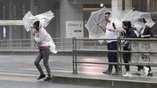 Rugby Pedestrians in Tokyo struggle with umbrellas in the wind and rain
