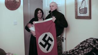 Claudia Patatas and Adam Thomas, holding their baby and a Swastika flag