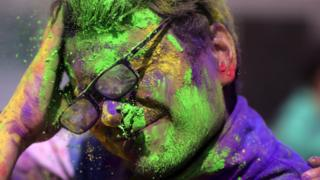A man is covered in colours by a friend
