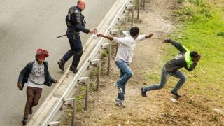 Un policier asperge du gaz lacrymogène à des migrants qui tentent d'accéder au tunnel sous la Manche, en juin 2015, dans le nord de la France.