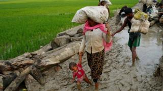 A Rohingya refugee woman holds her child as they walk on the muddy path after crossing the Bangladesh-Myanmar border in Teknaf, Bangladesh, 3 September 2017