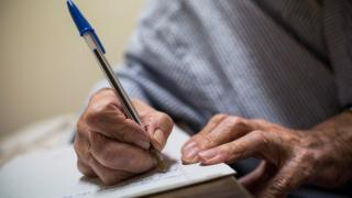 An elderly man writing, stock photo