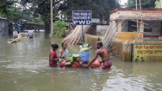 People wade through floodwater in Balurghat in West Bengal, India (17 Aug 2017)